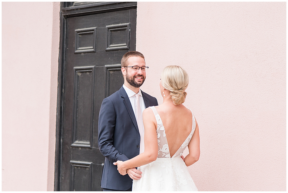 groom smiles at bride during first look on Charleston's Rainbow Row