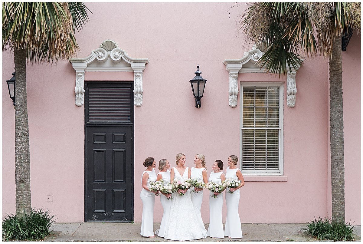 bride and bridesmaids pose by pink house in Charleston SC