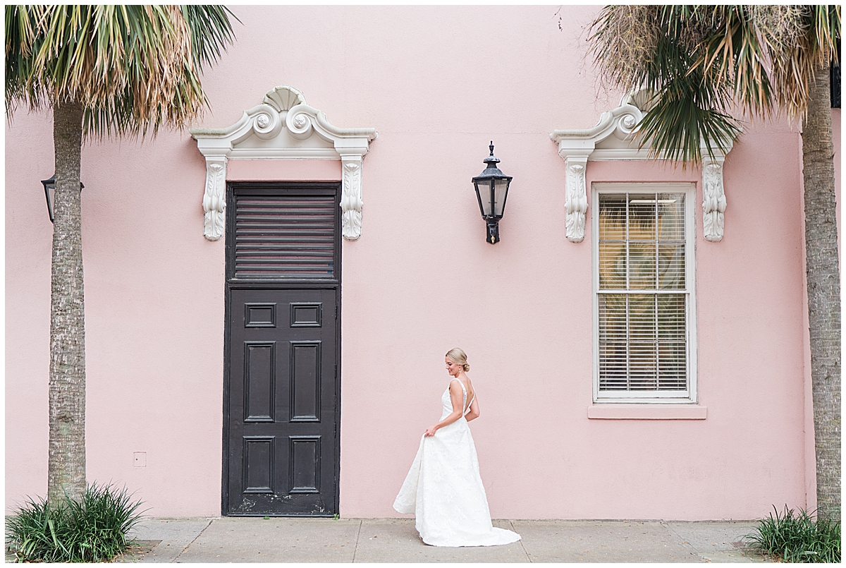bride twirls with wedding dress in front of Rainbow Row home