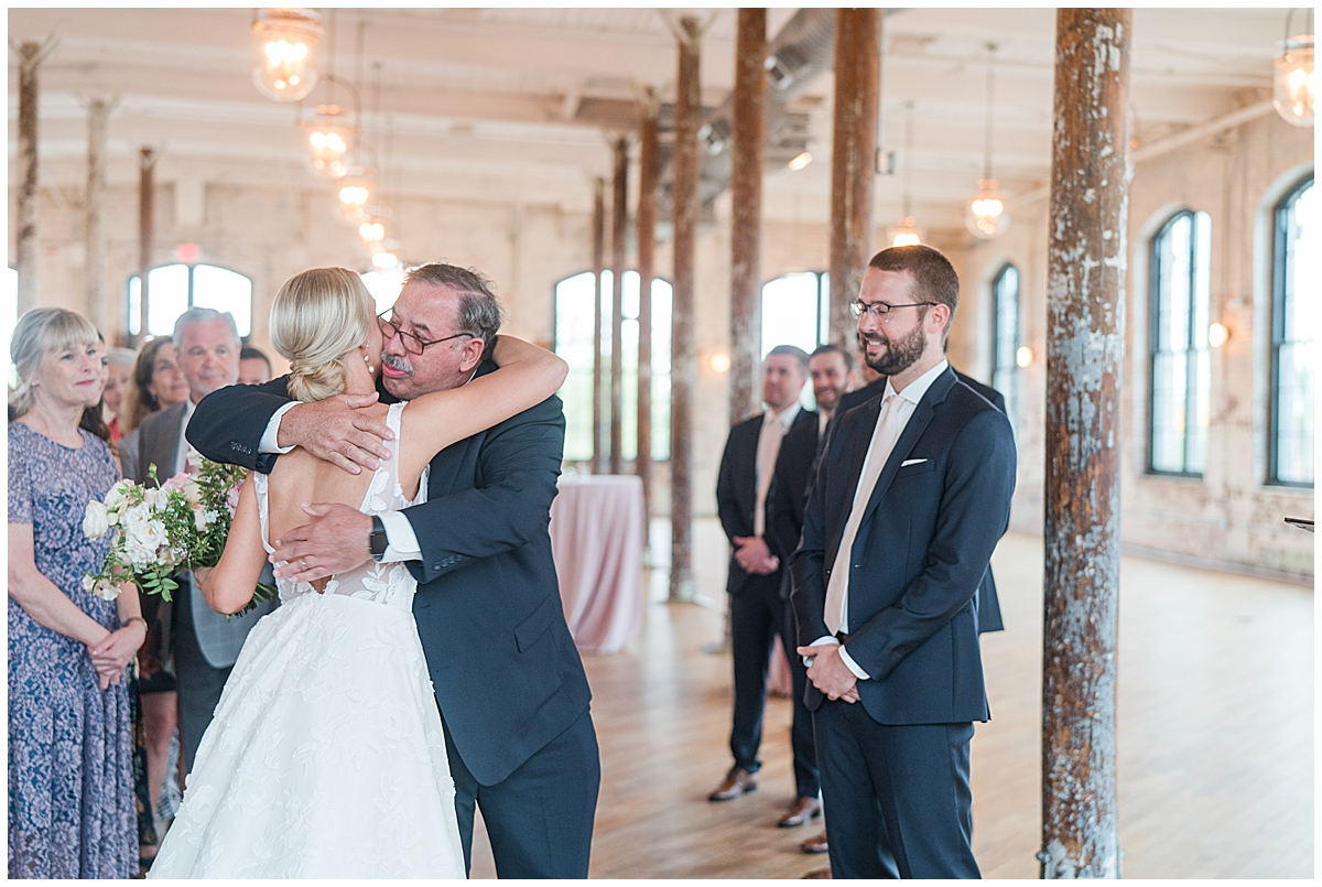 father hugs bride during ceremony