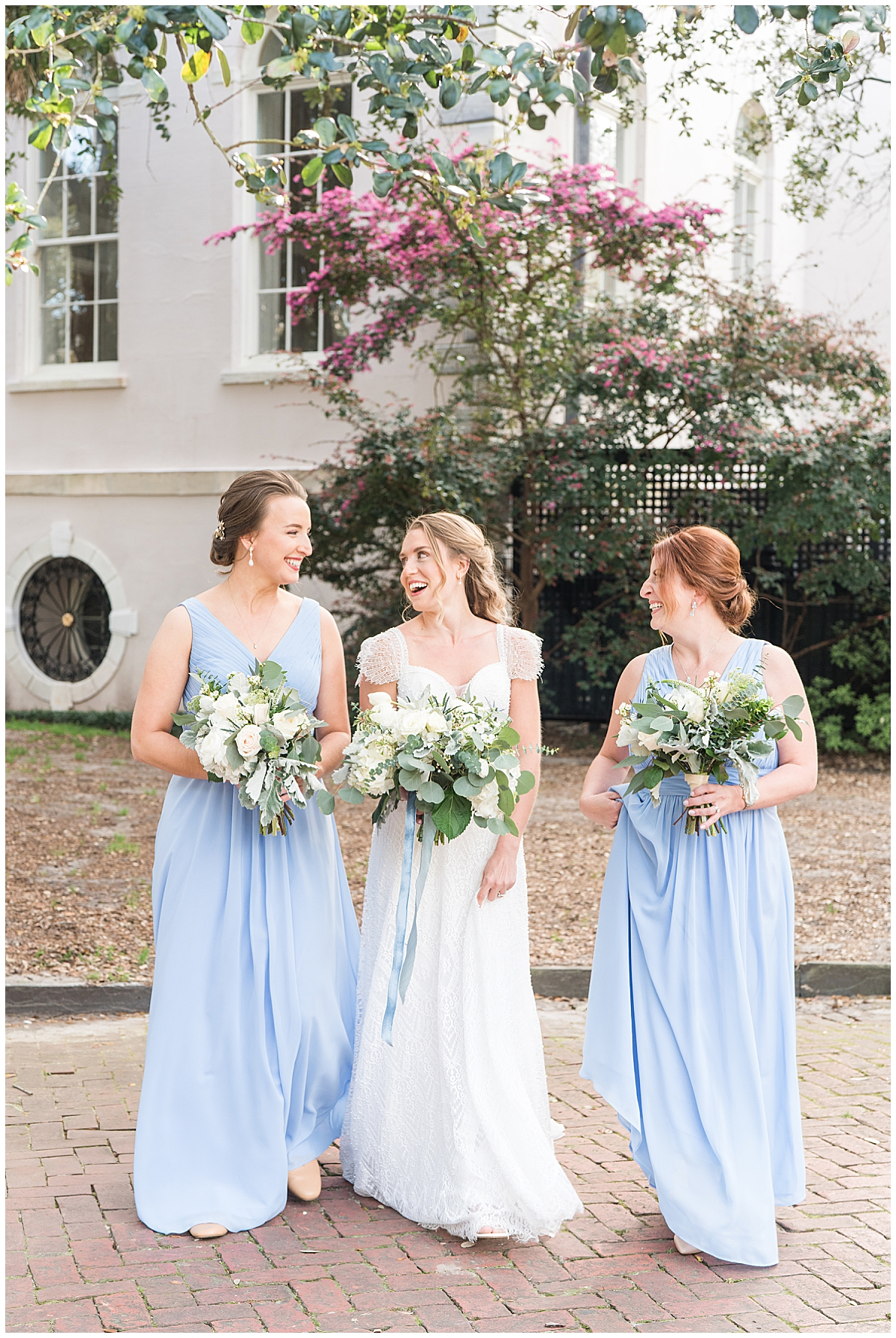 bride walks with bridesmaids in light blue gowns