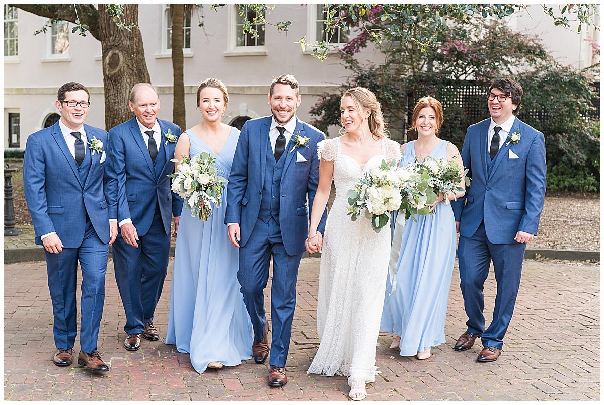 bride and groom walk with bridal party before Charleston Aquarium wedding