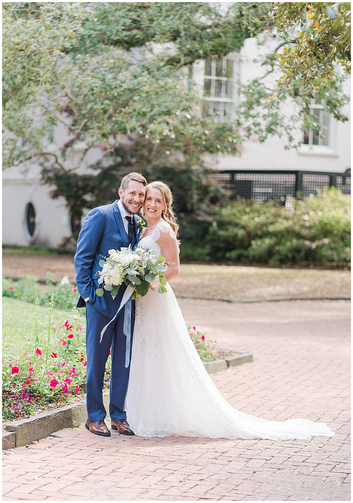 bride and groom lean against each other in Charleston park