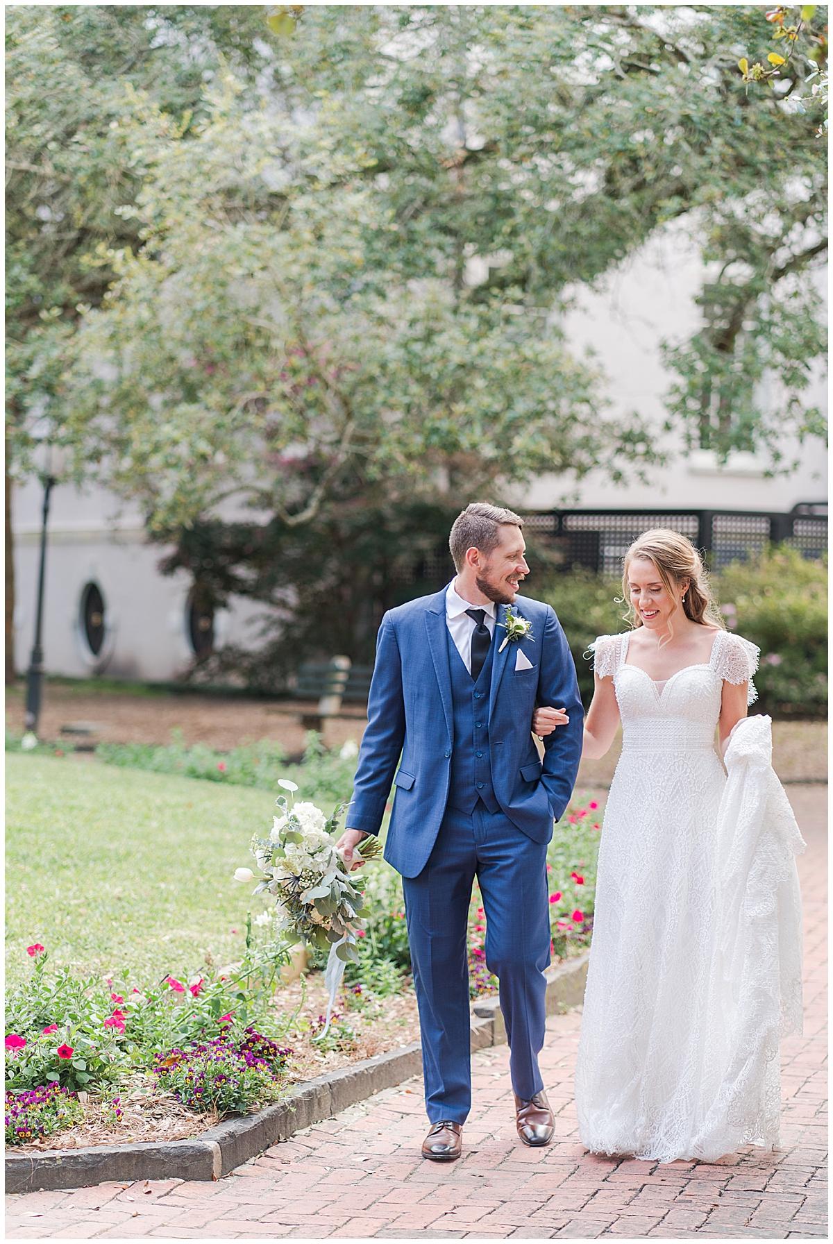 bride and groom walk through park in Charleston SC