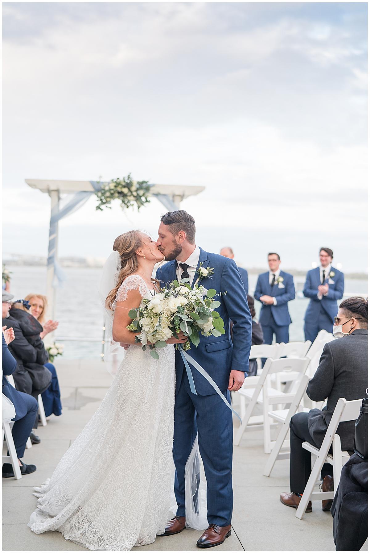 newlyweds kiss at end of aisle at Charleston Aquarium
