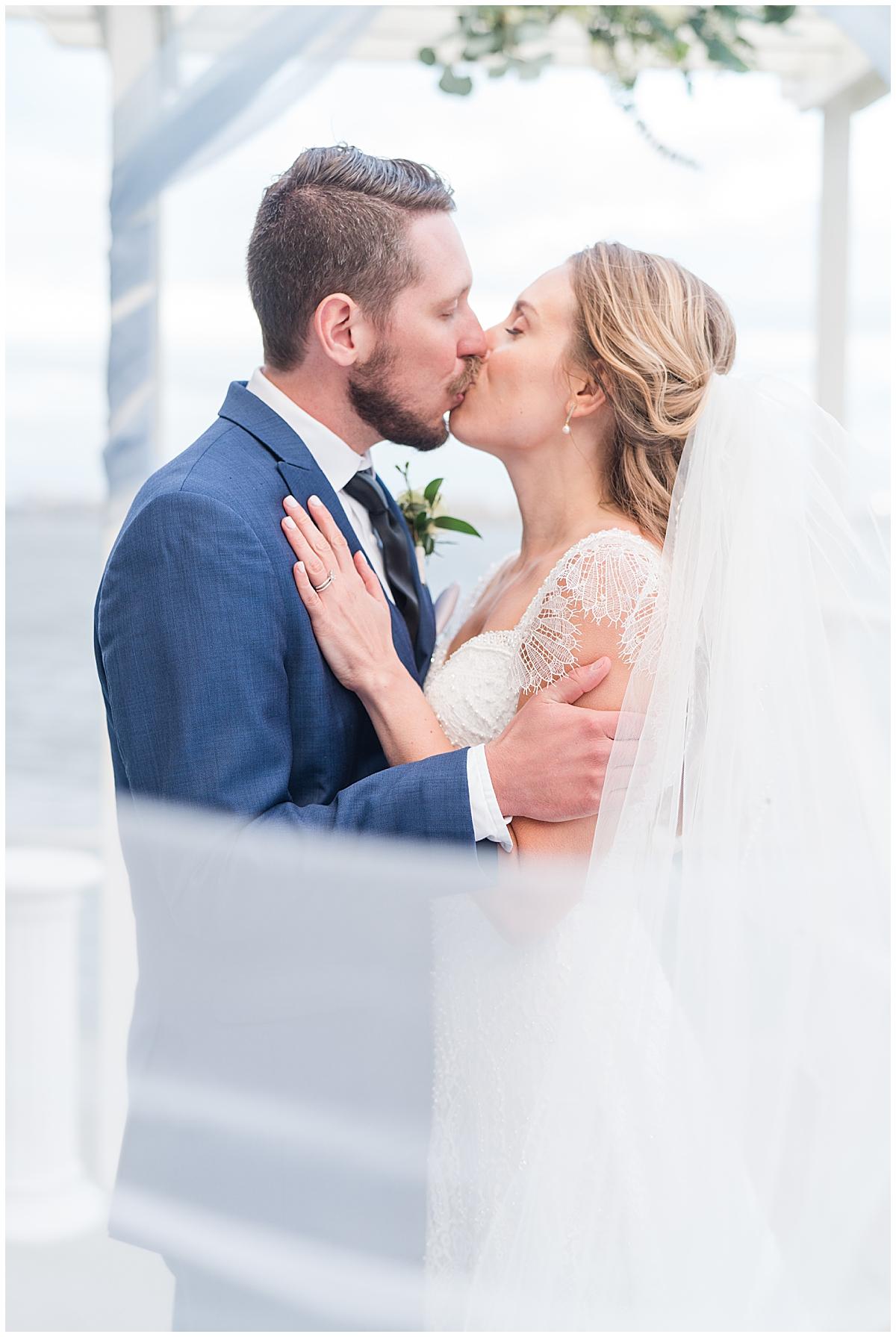 newlyweds kiss by arbor at Charleston Aquarium Wedding ceremony
