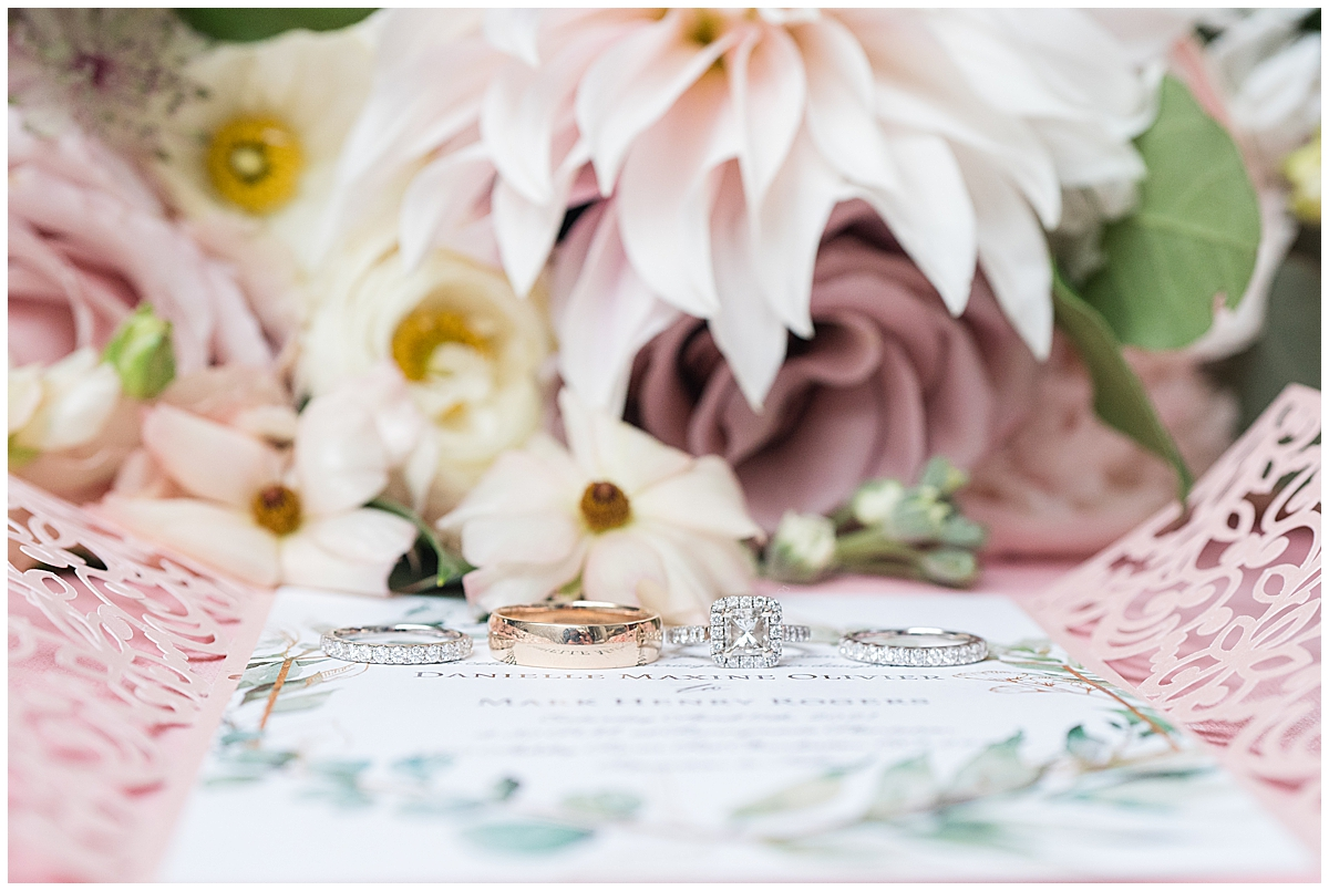 wedding rings rest on wedding invitation for spring ceremony