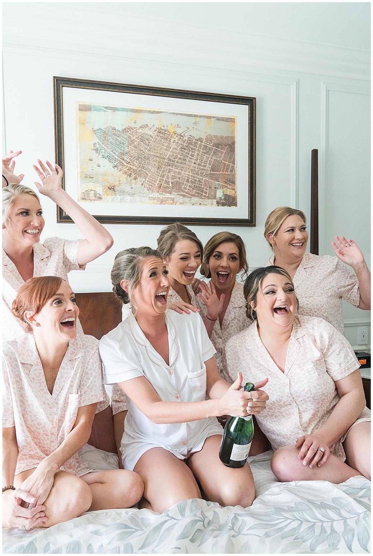 bride and bridesmaids pop champagne during South Carolina wedding prep