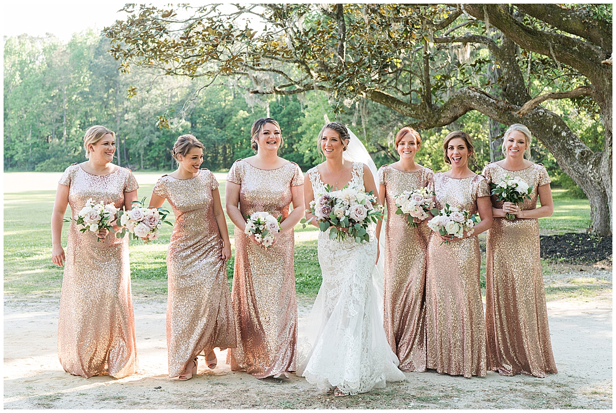 bride walks with bridesmaids in rose gold gowns