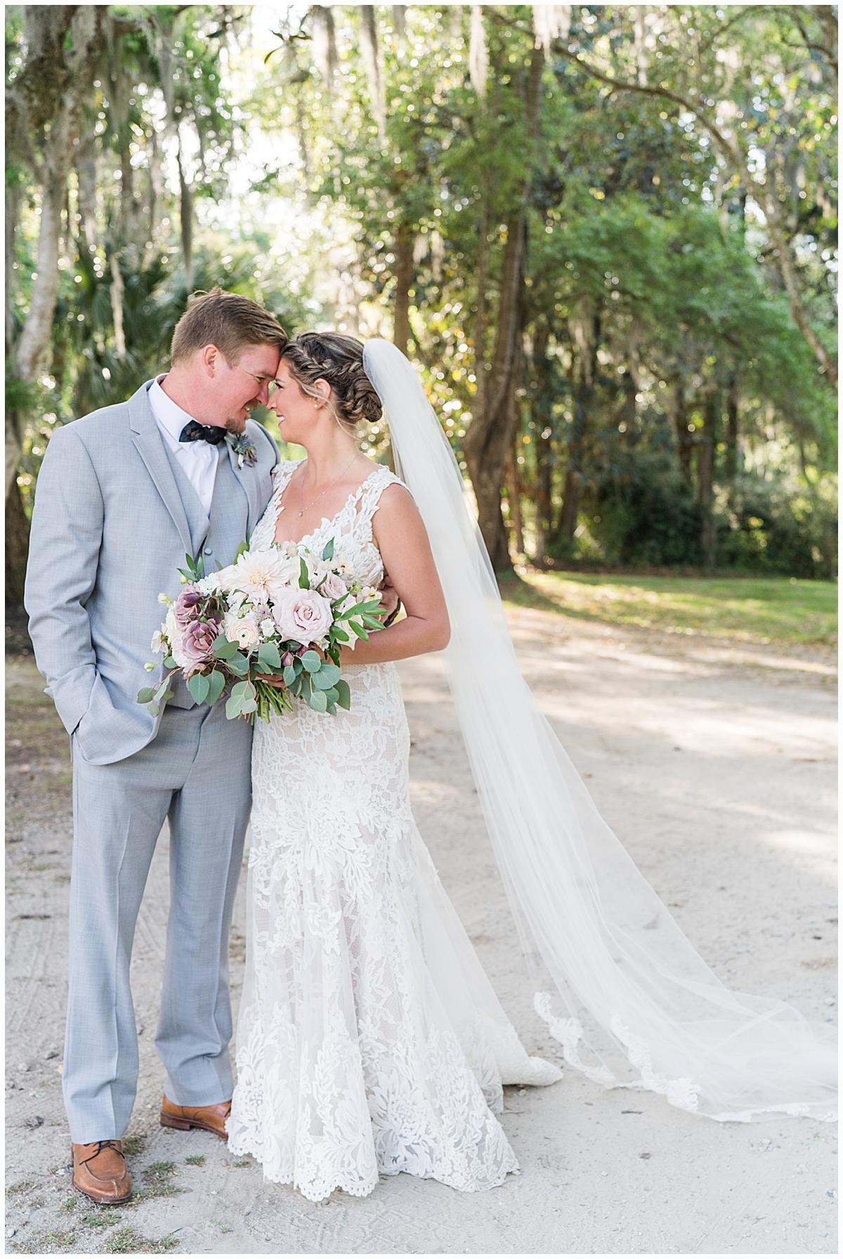 newlyweds pose on path during Charleston wedding photos