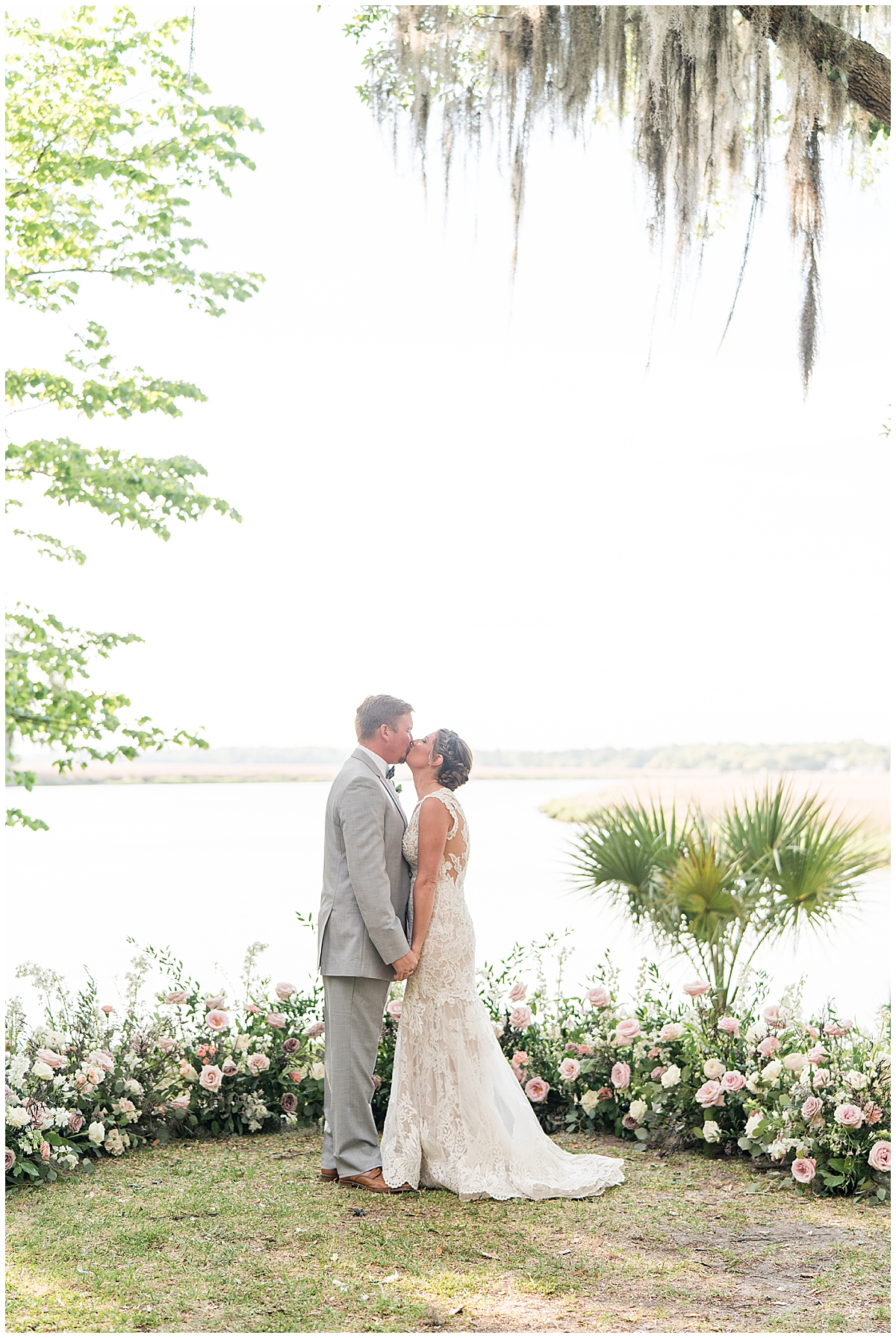 newlyweds kiss along water in Charleston