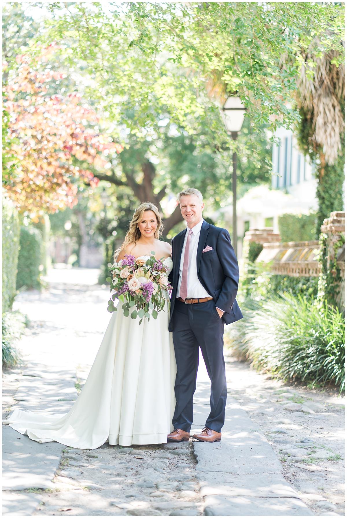 bride and groom pose on cobblestone street in Charleston SC