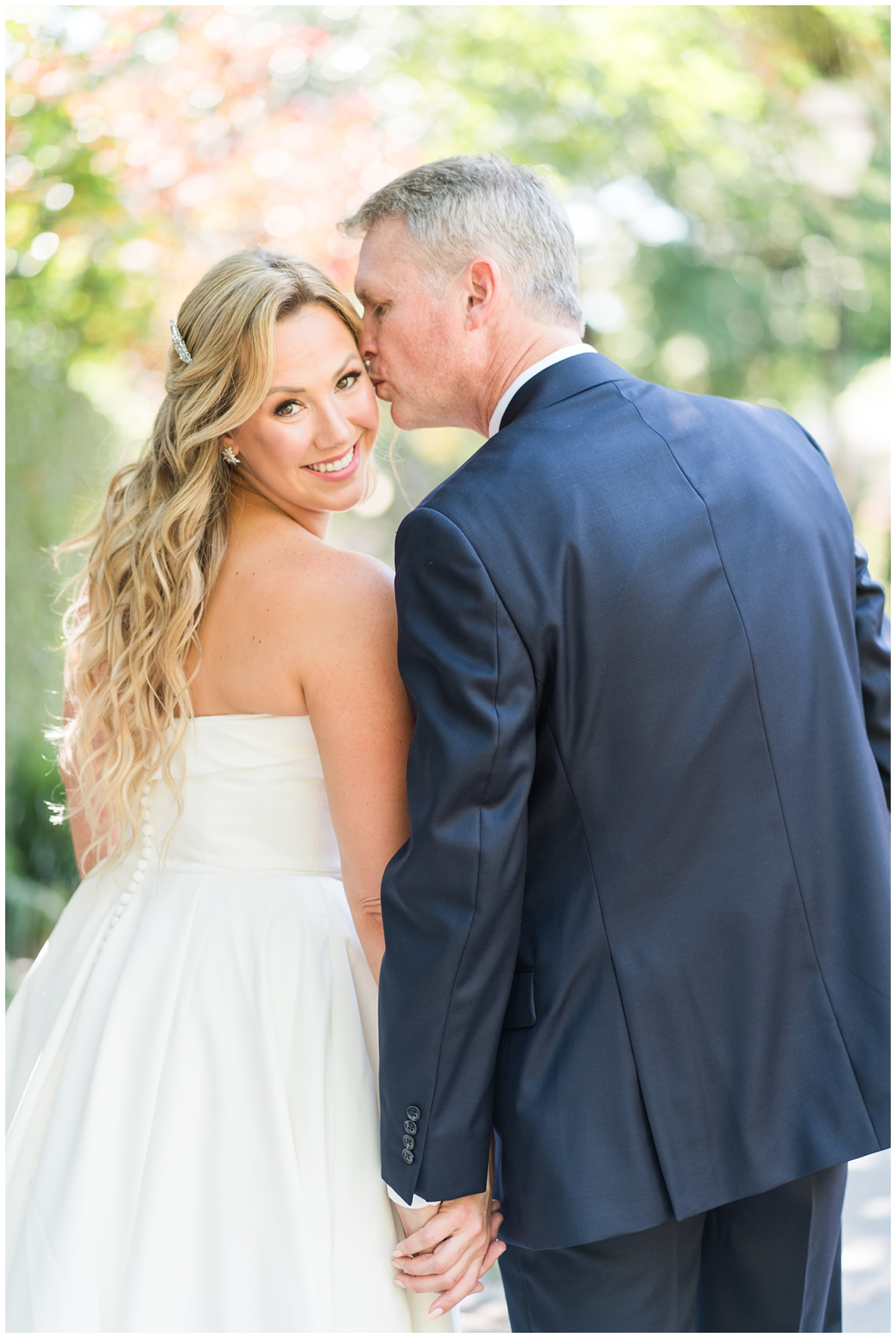 bride looks over shoulder in strapless gown while groom kisses forehead