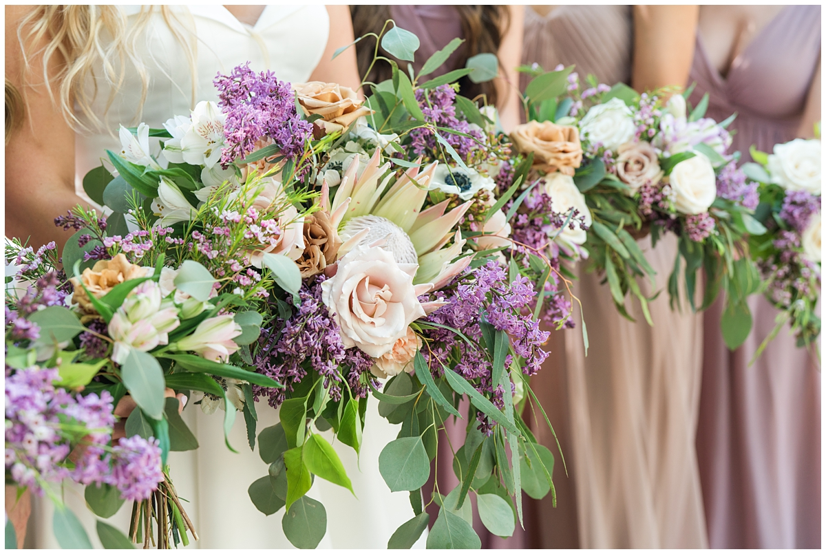 bride holds colorful bouquet for spring wedding