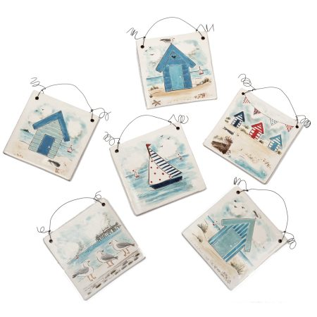 A photo of a selection of handmade ceramic Seaside design decorative tiles with wire for hanging. Priced individually, available in a variety of designs and colours.
