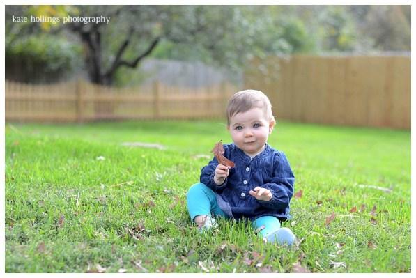 Baby girl sits outside in field
