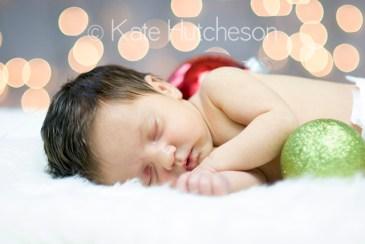 baby asleep on blanket with christmas ornaments