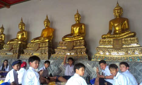 Eating lunch among the dozens of Buddhas at Wat Po. Each Buddha encases the bones of a deceased monk!