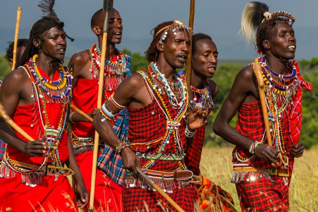 Maasai men dressed in traditional attire with spears and sticks singing and dancing at a cultural ceremony