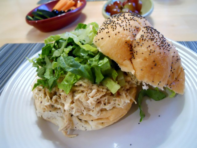 Pulled chicken with caesar dressing on a roll with lettuce.