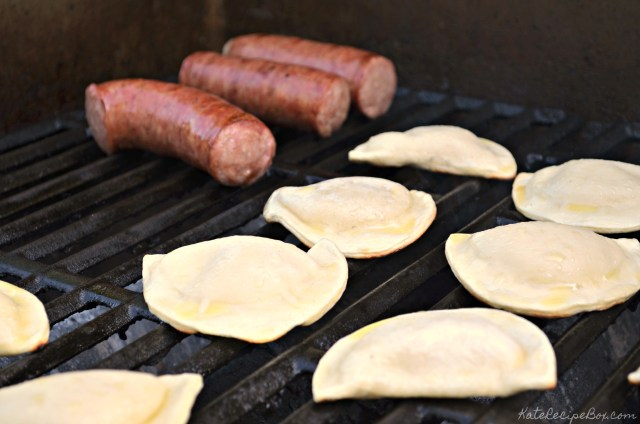 Kielbasa and pierogies being cooked on a grill grate.
