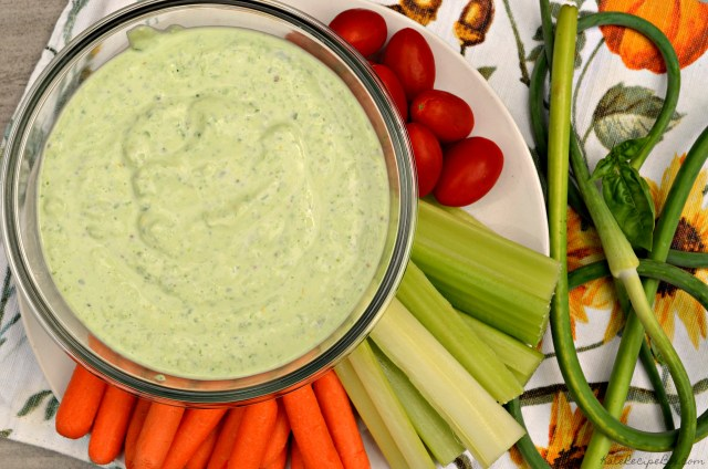 Top view of a bowl with green dip surrounded by raw baby carrots, celery sticks, and cherry tomatoes.
