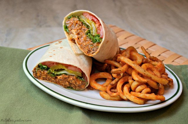 A flour tortilla filled with cooked ground beef, lettuce, tomatoes, and pickles. It's cut in half so you can see the filling and stacked on a white, oval plate with curly fries.