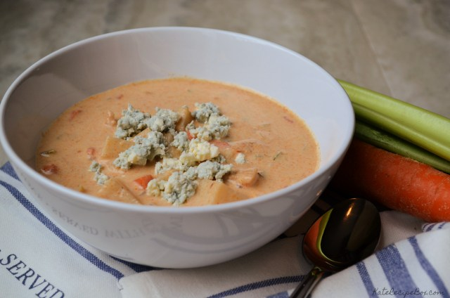 A bowl of golden chowder, with visible chunks of chicken, potatoes, and carrots. It's topped with crumbles of blue cheese.
