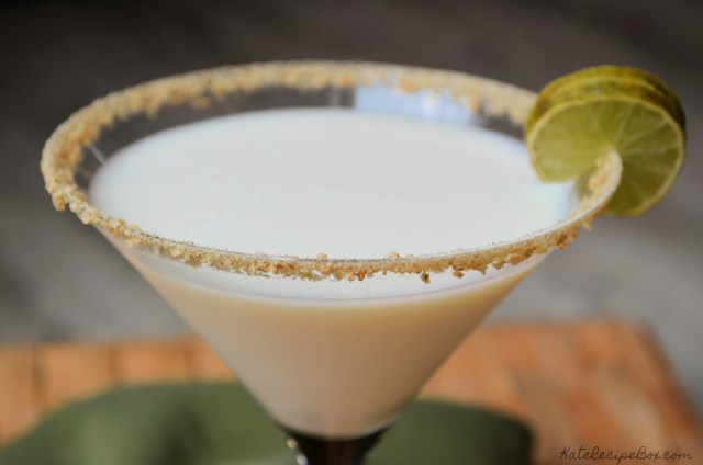 Key lime pie martini in a glass rimmed with crushed graham crackers and garnished with a lime.