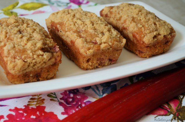 Three small loaves of crumb topped rhubarb bread on a plate.