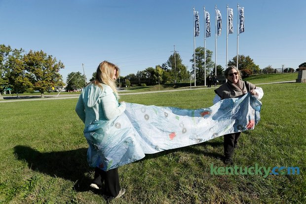 "Flag artist Kathleen O'Brien, right, and friend Laura Sullivan showed what one her flags looks like up close after a press conference unveiling flags ""Blazing"" the Legacy Trail at Lexmark near the Legacy Trail in Lexington, Ky., on Oct. 13, 2015. Photo by Pablo Alcala 