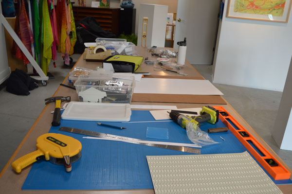 "A table of tools for installing art for ""Drawn to the Earth"""