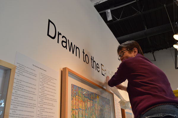 "Mary Rezny installs the vinyl title for ""Drawn to the Earth"""