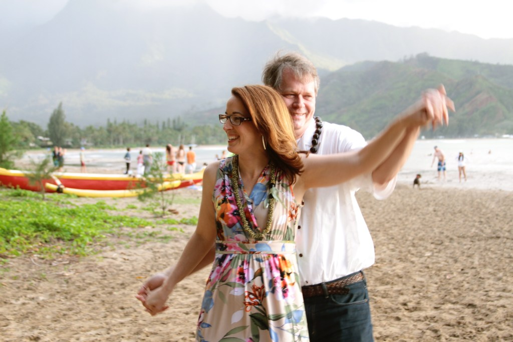 Kathy and Jim from The Trip Takes Us dance on the beach in Kauai. The Miles Makeover can help you get to YOUR dream destination.