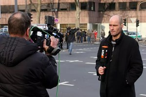 Photo of a reporter at work being filmed