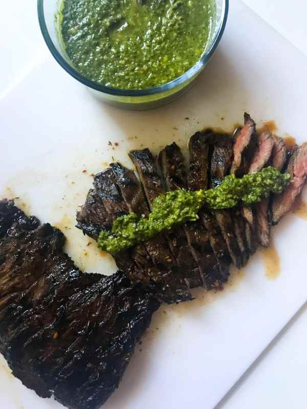 Basil Chimichurri provides the perfect pairing for the grilled skirt steak. The steak marinates (up to 24 hours) to amp up the flavor. A perfect summer meal that can be made almost entirely the day before. When you're ready to eat, just grill up the steak and you're good to go.