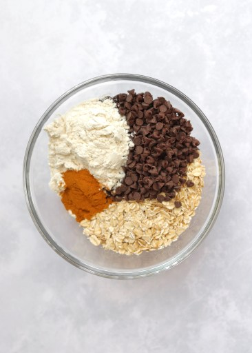 Oats, chocolate chips, flour, and cinnamon in glass bowl