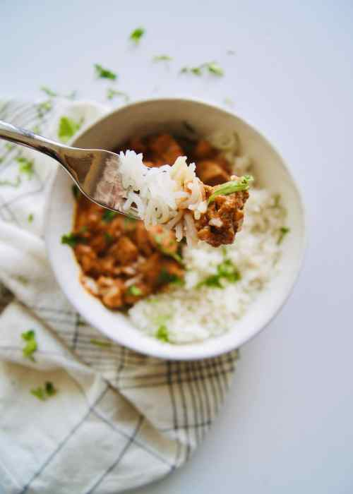 A forkful of butter chicken and white rice shown with the full bowl behind it
