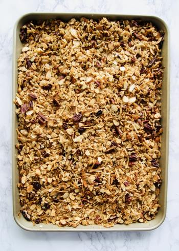 oats and nuts granola on a gold sheet pan