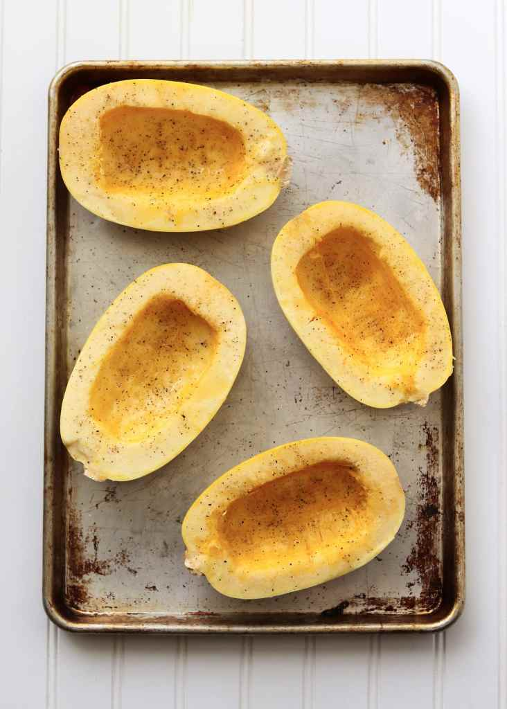 Spaghetti Squash halves with olive and salt and pepper on a sheet pan