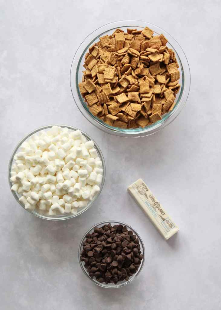 S'mores bars ingredients laid out. Cereal, marshmallows, chocolate chips, and a stick of butter.