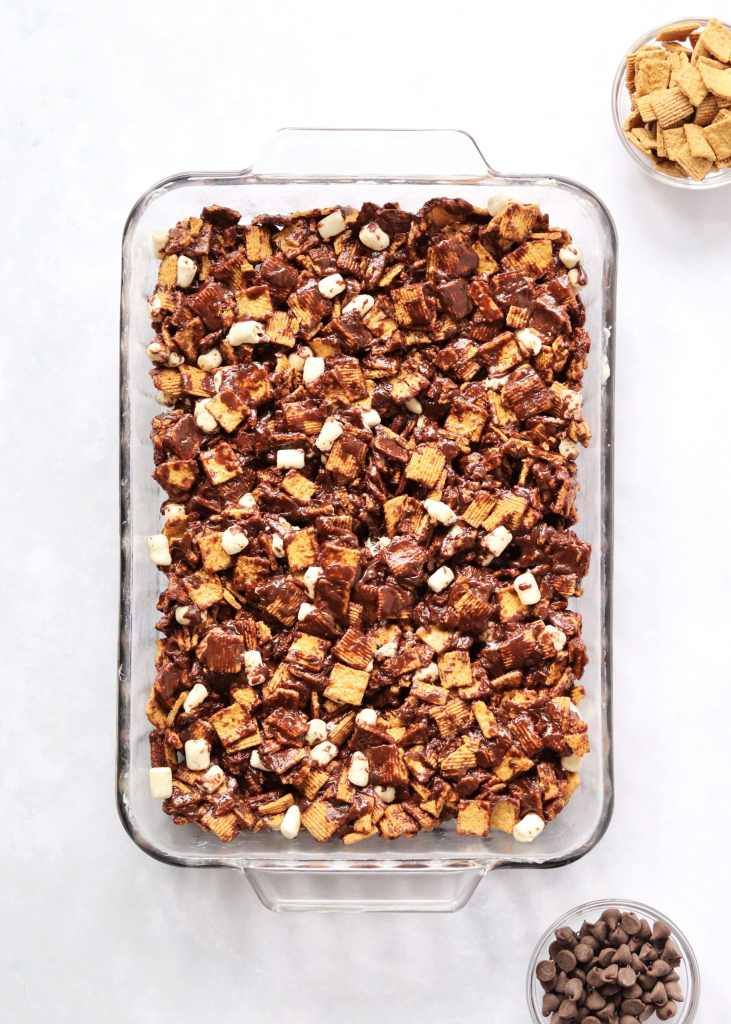 Cereal s'mores mixture pressed into a baking dish with small bowls of chocolate chips and cereal next to it.