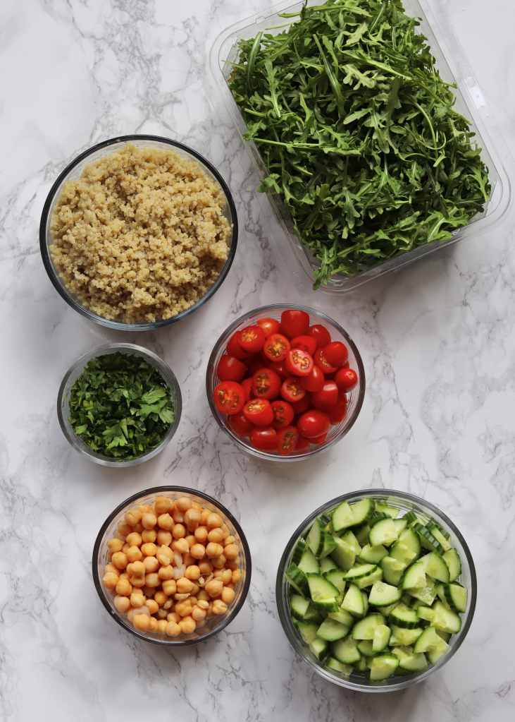 Arugula, Quinoa, tomatoes, parsley, chickpeas, and cucumber in individual bowls