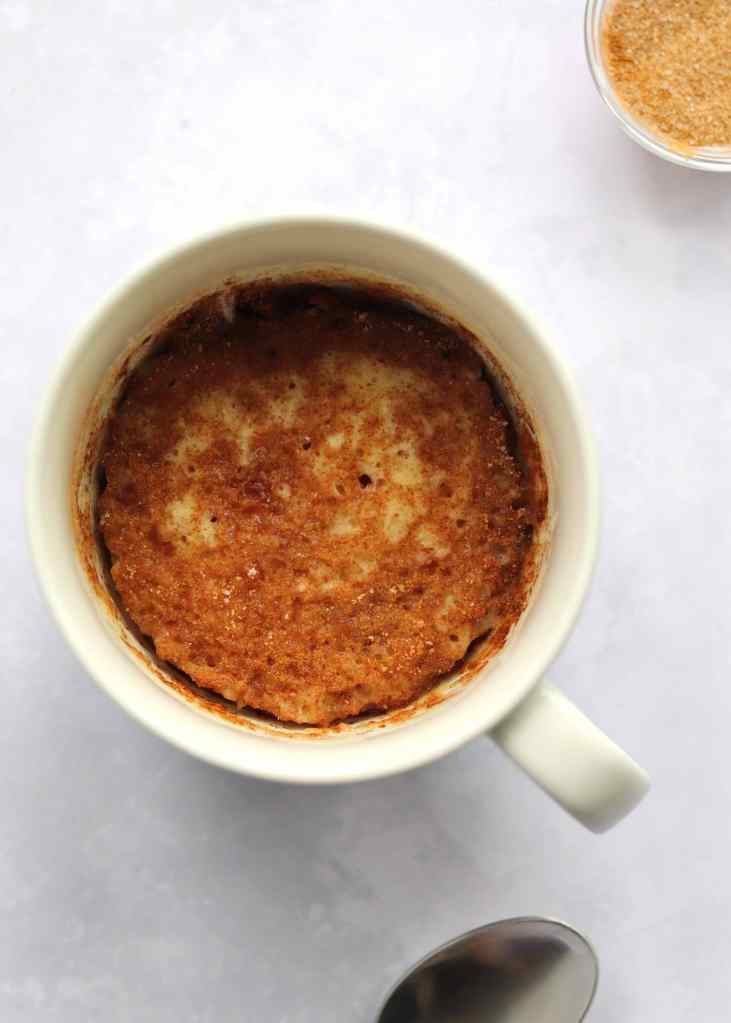 Coffee Cake in a mug with a spoon and extra cinnamon sugar next to it