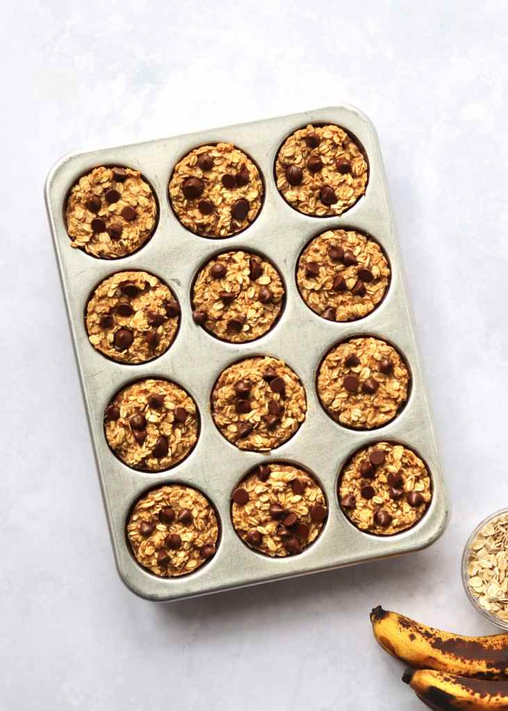 Baked Banana Oatmeal Cups in a muffin tin with ripe bananas and oats