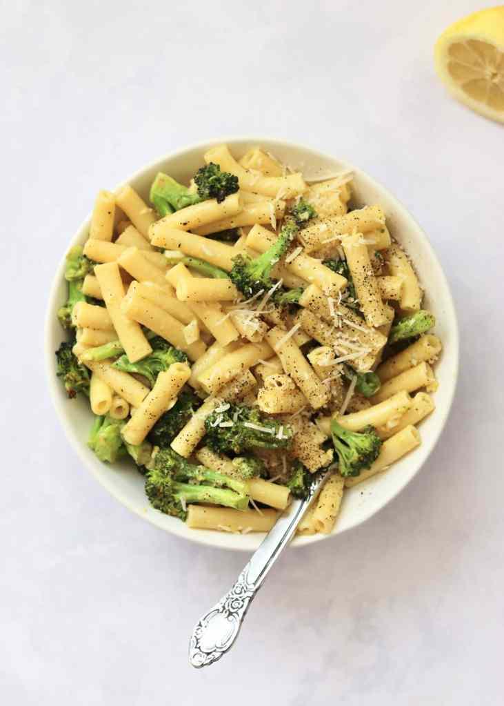 Broccoli carbonara pasta in white bowl with lemon