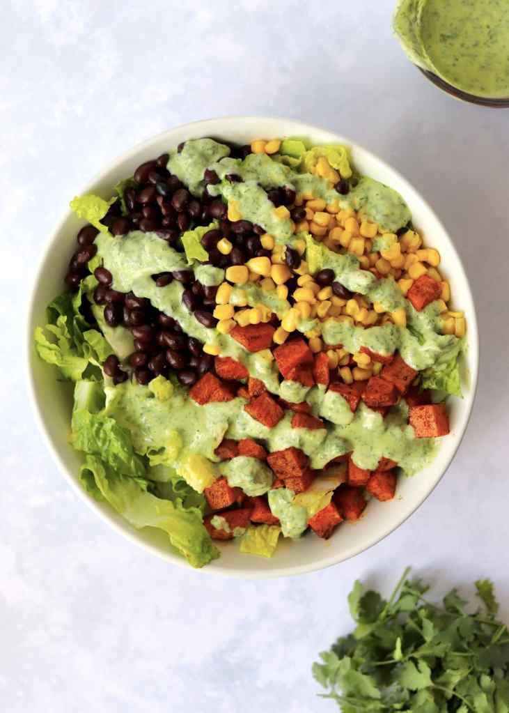 Sweet Potato Southwest Salad with greek yogurt dressing drizzled and bundle of cilantro