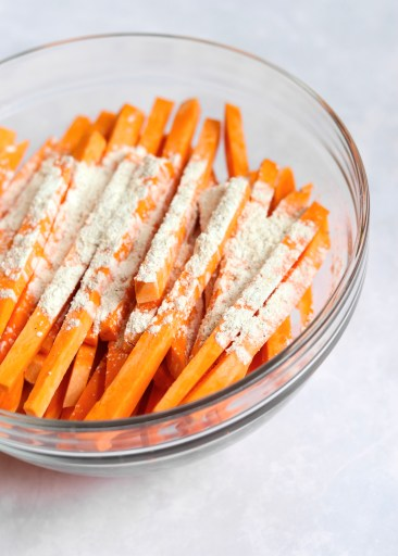 Cut sweet potatoes with cornstarch in glass bowl