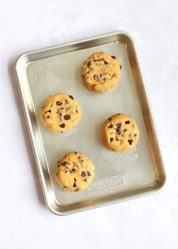 Formed discs of cookie dough on a light baking sheet
