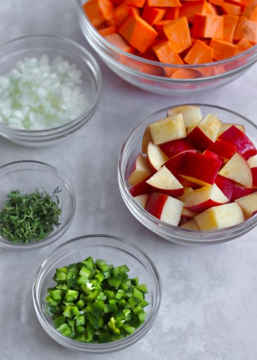 Ingredients in glass bowls - chopped sweet potato and apple, diced jalapeño, fresh thyme, and diced onion.